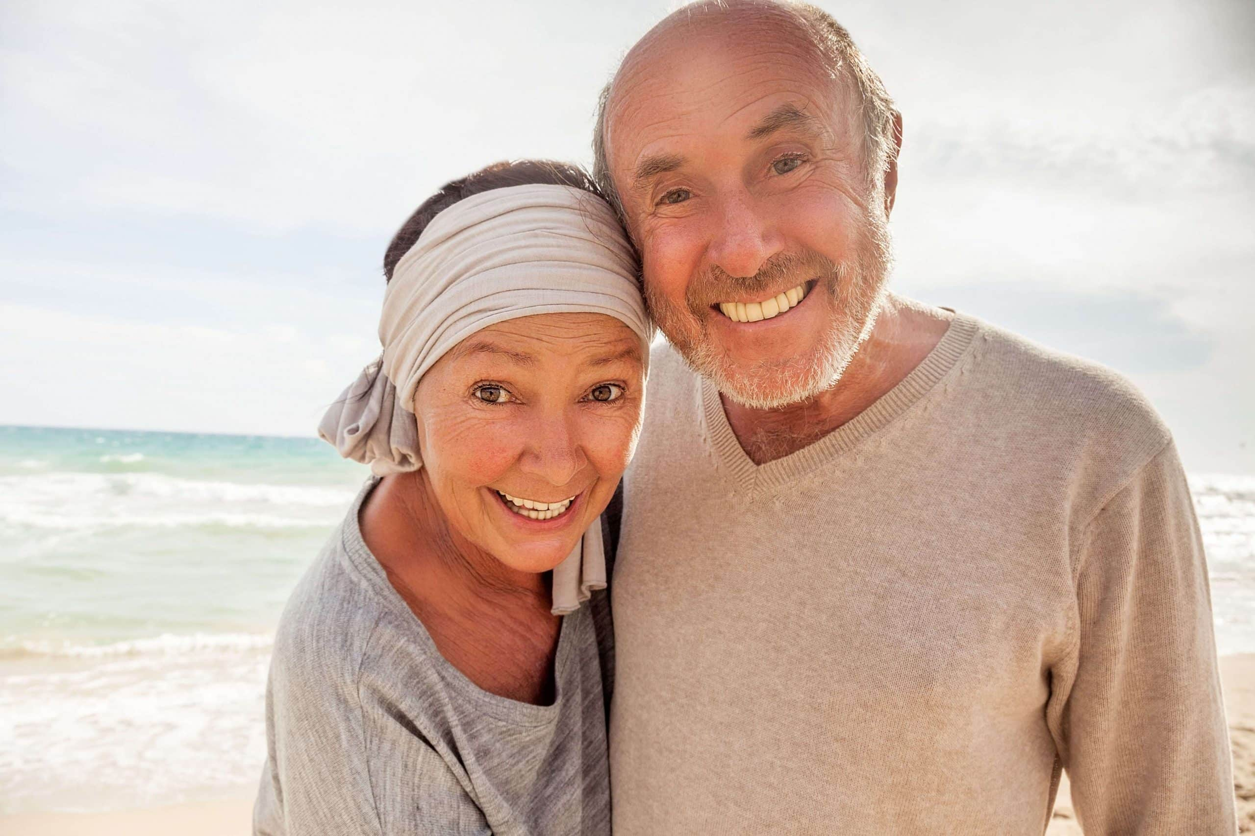 Smiling retired couple at the beach